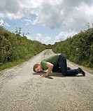 Man With Ear Pressed to Road Surface