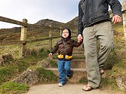 child walking with father on hill path