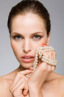 Female beauty model with pearls in hand