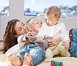 Mother and children cuddling and playing
