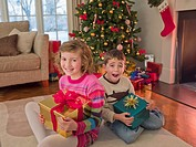Boy and girl holding Christmas gifts in living room