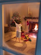 Boy with arms outstretched in living room near Christmas tree