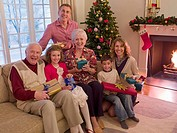 Multi_generation family holding gifts near Christmas tree