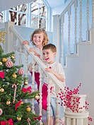 Boy and girl standing on stairs above Christmas tree