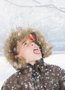 Boy sticking tongue out in snow