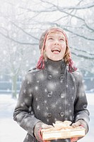 Snow falling on smiling girl holding Christmas gift