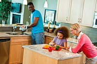Multi racial family preparing food in kitchen