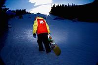 Snowboarder climbing up ski hill, Kananaskis, Alberta, Canada