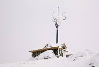 Snow covered building and satellite tower