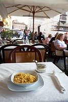 Bowl of Spagetti Carbonara and small bowl of parmesan cheese sitting on a table in a street cafe in the Piazza Navona Rome Lazio Italy