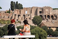 Two middle aged female tourists enjoy a picnic lunch in front of the Circus Maximus and the imperial palace on the palatine hill Rome Lazio Italy