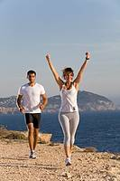 Couple jogging in a cliff by the sea in Ibiza