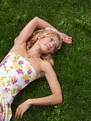 Young woman in summer dress lying on green grass