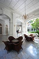 Singapore, view of the external lobby to the Raffles Hotel, with wicker tables and chairs designed by the architect Regent Alfred John Bidwell of Swan...