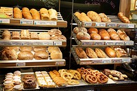 Assorted bread and pastries on shelves in a bakery
