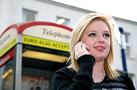 blonde haired female student smiling on mobile phone standing outside modern telephone box smiling