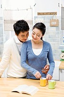 Young couple in the kitchen, making tea