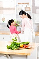 Girl and mother in kitchen