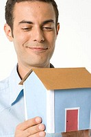Close_up of a young man looking at a model of a home and smiling