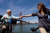 Mature couple holding hands with a suspension bridge in the background, Golden Gate Bridge, San Francisco, California, USA