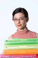 Portrait of a businesswoman holding a stack of ring binders