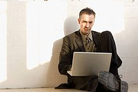 Businessman sitting on the floor and using a laptop