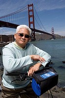 Mature man leaning on a bicycle with a suspension bridge in the background, Golden Gate Bridge, San Francisco, California, USA