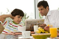 Close_up of a mature man reading a newspaper with his son at a breakfast table