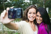 Two women taking picture of themselves with digital camera