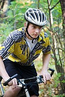 Teenage boy riding a mountain bike in a forest