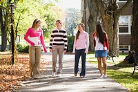 Four students walking together and smiling