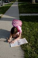 Canada, Ontario, Windsor. An eight year old girl with a pink knapsack writes in a notebook on a sidewalk