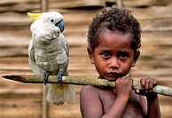 Papua New Guinea, Trobriand Islands, child´s portrait with a cockatoo
