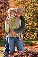 Senior couple doing yard work in autumn