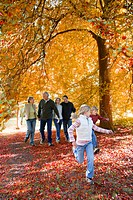 Three generation walking in park in autumn