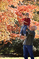 Man lifting son in park in autumn