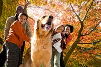African family walking dog in park in autumn