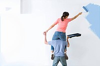 Woman sitting on mans shoulders and painting wall with paint roller