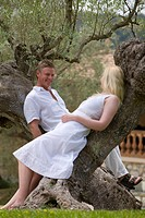 Couple leaning on olive tree trunks