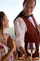 Waiter serving food to woman at patio table