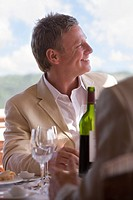 Smiling man sitting at patio table with wine glasses