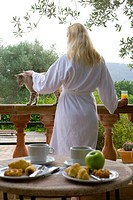 Woman in bathrobe petting cat on patio with breakfast in foreground