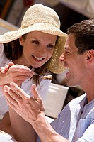Woman feeding man ice cream at outdoor cafe
