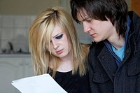 young teenage couple intently reading a document together in the kitchen of their bedsit