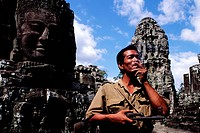 Cambodia, Angkor, soldier smoking a cigarette while he is taking care of Bayon temple against looters