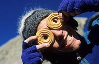 A young man plays with two biscuits by placing them in the eyes and smile