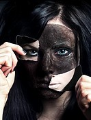 The face of a young woman disguised by a painted mask