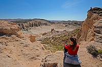 Woman and teenager sit at edge of desert canyon and look at view, Red Rock Canyon, California, USA
