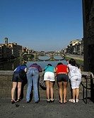 Five girls look down from Ponte Vecchio bridge over the River Arno in the Tuscan city of Florence or Firenze in Italy with the Ponte Santa Trinita in ...