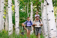 Family hiking together in aspen forest Utah USA